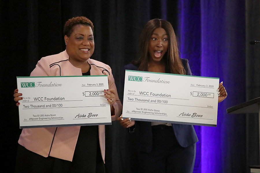 Aisha Bowe and Kim Hurns holding checks to WCC Foundation from Bowe